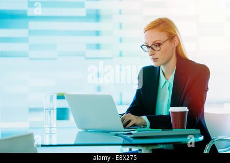 Geschäftsfrau, die Arbeiten am Laptop in Bürogebäude café - Stockfoto