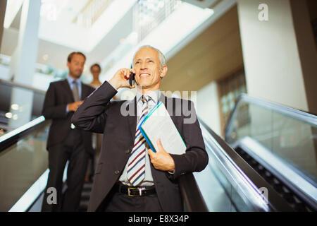 Geschäftsmann, reden über Handy Rolltreppe hinunter - Stockfoto
