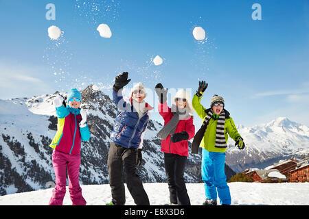 Familie werfen Schneebälle auf Berggipfel - Stockfoto