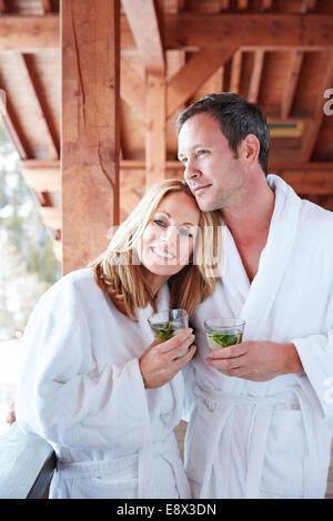 Paar im Bademantel umarmt auf Balkon - Stockfoto