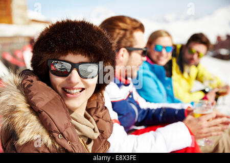Frau sitzt mit Freunden im Schnee - Stockfoto