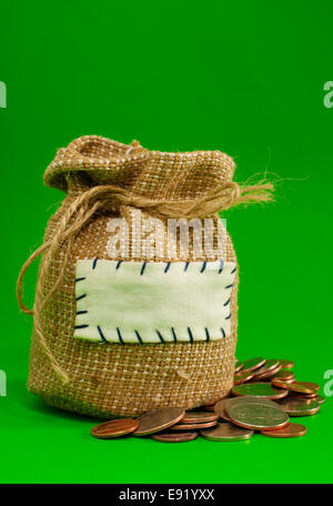 Sack voller Münzen auf grünem Hintergrund - Stockfoto