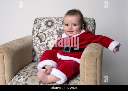 9 Monate altes Baby junge Santa Anzug, grinsend und auf einem Stuhl sitzend - Stockfoto