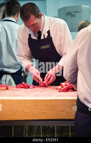 Ein Metzger Schneiden von Fleisch an der Theke - Stockfoto