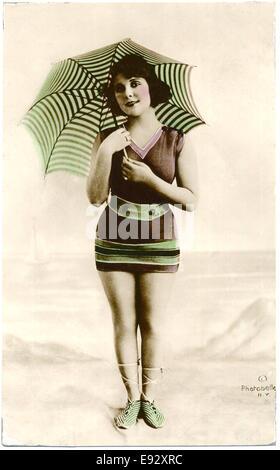 Frau im Badeanzug braun, gestreifte Sonnenschirm und grün gestreifte Schuh stehen am Strand, handkolorierten, Postkarte, - Stockfoto