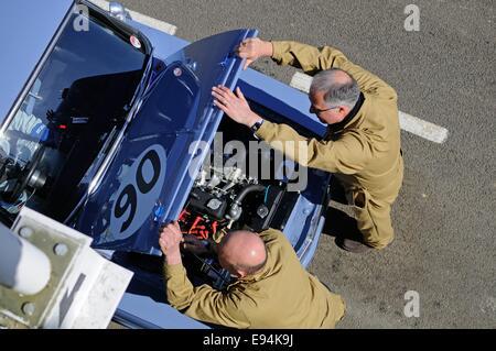 Overhead Schuss von zwei Mechanikern in der Boxengasse in Goodwood Öffnung der Motorhaube eines Rennwagens Fiat - Stockfoto