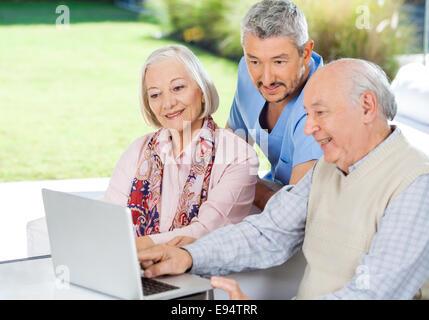 Hausmeister beobachtete älteres Paar mit Laptop - Stockfoto