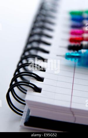 zurück zu Schule-Versorgungsmaterialien helle Multi farbige Stifte und ein Spiral-Notizbuch - Stockfoto