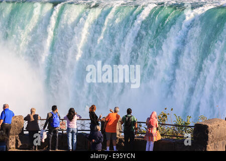 Touristen mit Blick auf und genießen den Blick auf den Horseshoe Falls, Teil von Niagara Falls, Ontario, Kanada. - Stockfoto