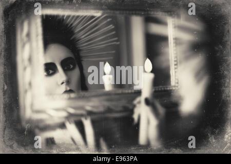 Schöne Goth Mädchen halten Kerze in der hand und Blick in den Spiegel. Grunge-Textur-Effekt - Stockfoto