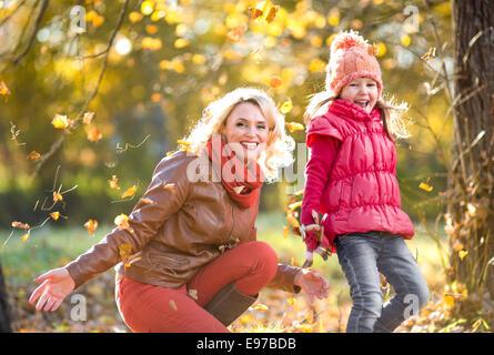 Glückliche Eltern und Kind im freien Spiel mit gelben Blätter im Herbst