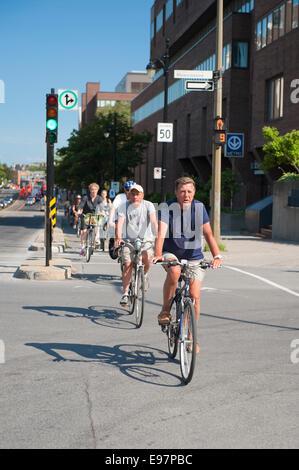 Radfahrer auf einem Radweg in der Innenstadt von Montreal, Québec, Kanada reisen. - Stockfoto