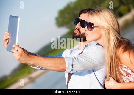 Junges Paar unter einem Porträt mit digital-Tablette - Stockfoto