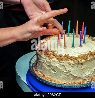 Auf schwarzem Hintergrund Hände zwei Beleuchtung 9 bunte Geburtstagskerzen auf Toffee Geburtstag Kuchen Streichholz. - Stockfoto