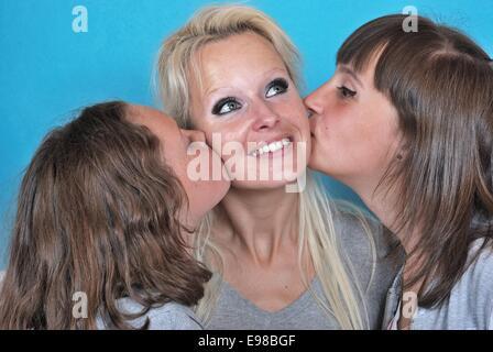 Eine Mutter lächelt, als sie einen Kuss auf die Wange von ihren jungen Töchtern erhält - Stockfoto