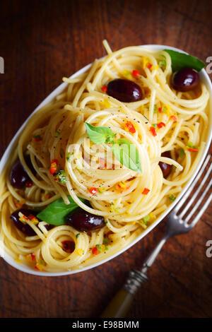 Draufsicht der Spaghetti Nudeln mit Oliven in einer Schüssel mit einer Gabel einstechen. - Stockfoto