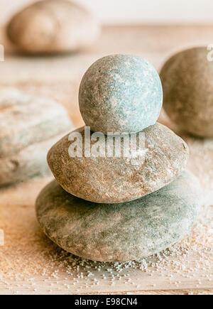 Gestapelte natürlichen gerundet verwitterte Zen Steinen mit verstreuten Strandsand konzeptionelle von Spa, Wellness, - Stockfoto