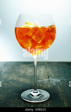 Gekühlte tropischen Aperol, Rum und Orange cocktail in einem eleganten Glas Wein auf einer hölzernen Theke in einer Bar oder einem club