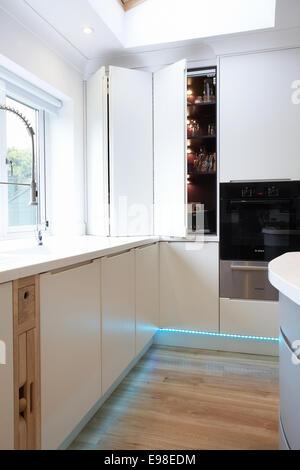 Eine klappbare Schranktür öffnen in einer modernen Küche im ...