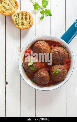 Leckere herzhafte Boden Rindfleisch Frikadellen in Tomatensauce serviert in einem Topf mit knusprig geröstetem Kräuterbrot - Stockfoto