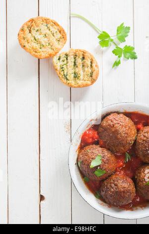 Pikante Rindfleisch Frikadellen in einer würzigen Tomatensauce mit frischen Kräutern, serviert in einem Topf mit - Stockfoto
