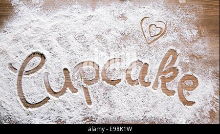 Mehl Artwork mit Essen und Handabdrücke, Spaß-Hintergrund mit dem Wort CUPCAKE und menschlichen Handpints in verstreuten - Stockfoto