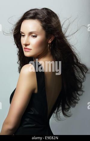 Charme. Aristokratische Dame im schwarzen Kleid und wallendem Haar - Stockfoto