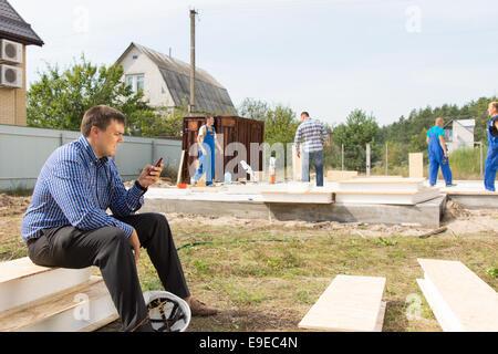 Männliche Bauleiter beschäftigt Messaging mit seinem Handy im Projektgebiet. - Stockfoto