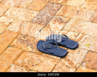 Ausrangierte Flipflops auf gepflasterten Terrasse pool - Stockfoto
