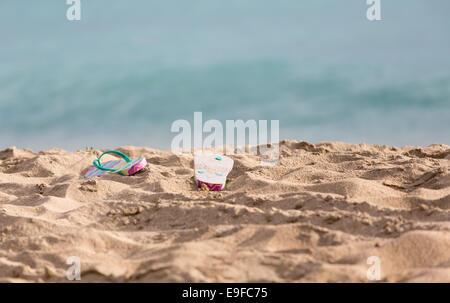 Ausrangierte Flipflops am Sandstrand vom Ozean - Stockfoto