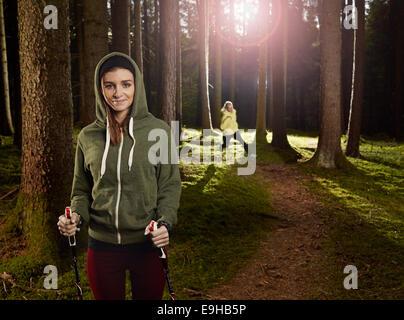Frau mit Nordic Walking Stöcke im Wald, eine andere Frau Joggen im Rücken, Tirol, Österreich - Stockfoto