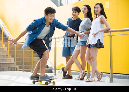 Junger Mann mit Freunden skateboarding - Stockfoto