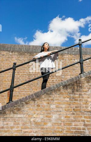 Niedrigen Winkel Blick der jungen Frau, die wegsehen und stützte sich auf Geländer gegen bewölktem Himmel