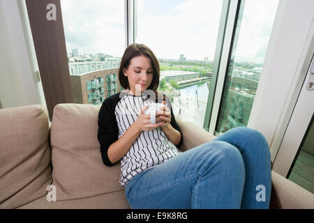 Schöne Frau mit Kaffee zu Hause auf sofa - Stockfoto