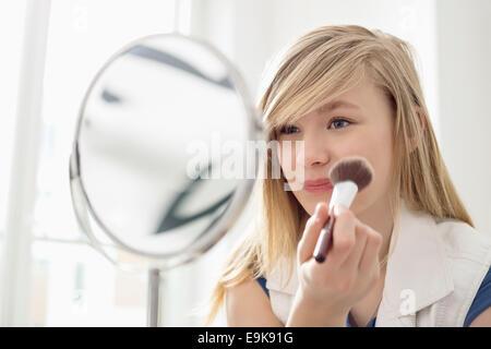 Mädchen beim Schminken vor dem Spiegel zu Hause - Stockfoto
