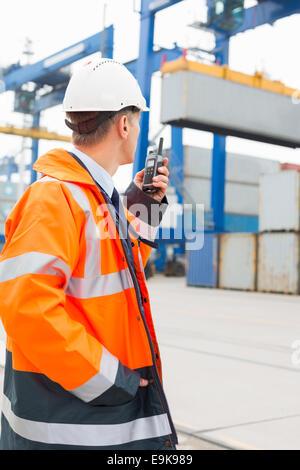 Mann mittleren Alters mit Walkie-talkie im Frachthafen - Stockfoto