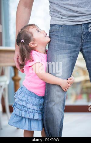 Seitenansicht des Mädchens, die Umarmung des Vaters Bein im Haus - Stockfoto