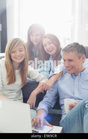 Glückliche Eltern mit Töchtern mit Laptop im Wohnzimmer - Stockfoto