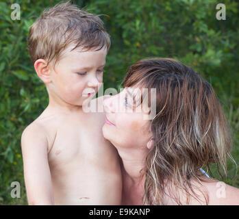 Junge Frau mit ihrem kleinen Sohn nach dem Baden im Fluss. - Stockfoto