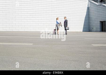 Geschäftsleute mit Gepäck reden auf Straße - Stockfoto