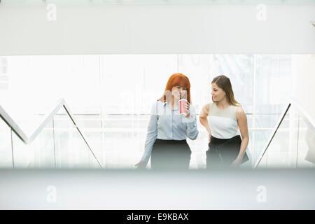 Geschäftsfrauen Kaffeetrinken während der Bewegung Stufen im Büro - Stockfoto