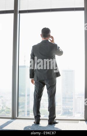 Voller Länge Rückansicht des Reifen Geschäftsmann mit Handy-weiß stehen in der Nähe von Fenster - Stockfoto