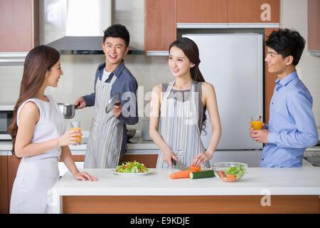 Junges Paar, Kochen und sprechen mit ihren Freunden in der Küche - Stockfoto