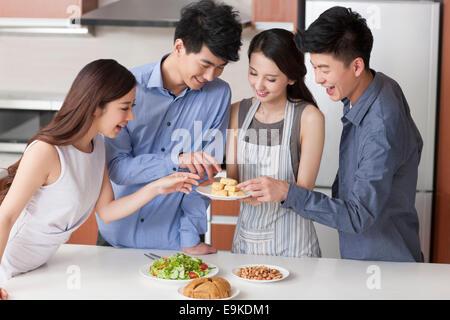 Junge Frau für ihre Freunde in der Küche kochen - Stockfoto
