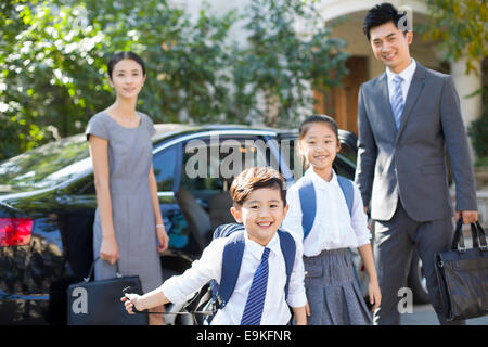 Junges Paar, die ihre Kinder von der Schule zurück bringen - Stockfoto