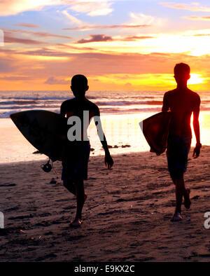 Zwei Surfer am Ocean Beach bei Sonnenuntergang auf der Insel Bali, Indonesien - Stockfoto