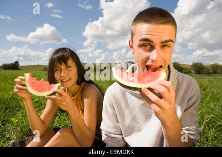 Junges Paar Essen Wassermelone im Feld - Stockfoto