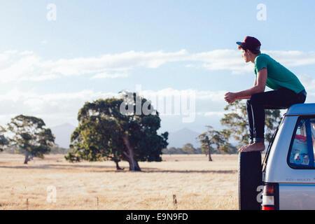 Junger Mann sitzt auf dem Auto, Grampians Nature Reserve, Australien - Stockfoto