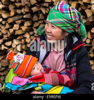 Glücklich Hmong Frau mit Baby, Lächeln, draußen zu sitzen am Ta Van Dorf in der Nähe von Sapa, Provinz Lao Cai, - Stockfoto
