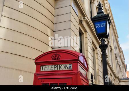 Eine traditionelle britische rote Telefonzelle durch eine alte Polizei Laternenpfahl in der Stadt von London, England, - Stockfoto